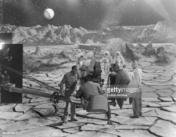 Actors wearing spacesuits walk on a replica of the lunar surface as director Irving Pichel and a cinematographer sit on a camera crane preparing to...