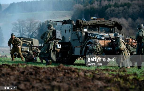Actors wearing WWII German unifoms fight with one wearing a WWII US uniform during a historical re-enactment of the Battle of the Ardennes as part of...