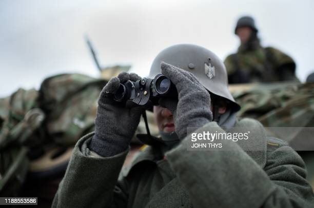 Actors wearing WWII German uniforms take part in a historical re-enactment of the Battle of the Ardennes as part of commemorations marking the 75th...