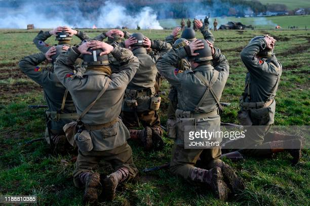 TOPSHOT Actors wearing WWII US unifoms surrender to actors wearing WWII German uniforms during a historical reenactment of the Battle of the Ardennes...