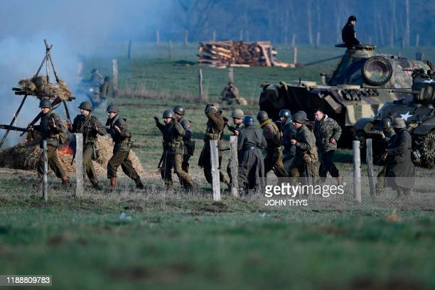 Actors wearing WWII US uniforms surrender to actors wearing WWII German unifoms during a historical reenactment of the Battle of the Ardennes as part...