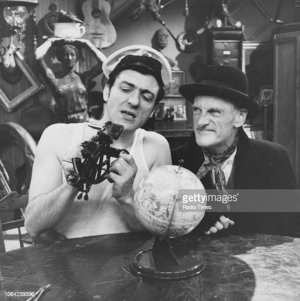 Actors Wilfrid Brambell and Harry H Corbett sitting in front of a globe in a scene from episode 'Homes Fit for Heroes' of the television sitcom...