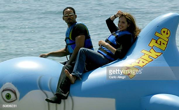 Actors Will Smith and Angelina Jolie participate in a stunt during a photocall for the film 'Shark Tale' during the 57th International Cannes Film...