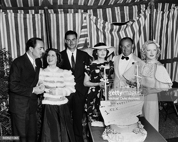 Actors William Powell Norma Shearer Errol Flynn Kay Francis Jack Warner and Marion Davies poses with a cake in Los Angeles California