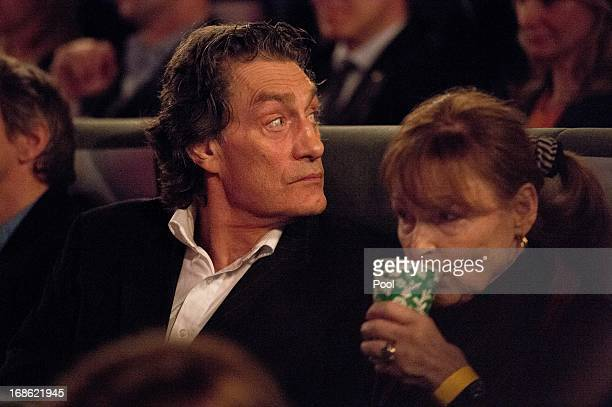 Actors Winfried Glatzeder and Angelica Domroese look on from the audience as German Chancellor Angela Merkel speaks prior to the screening of the...