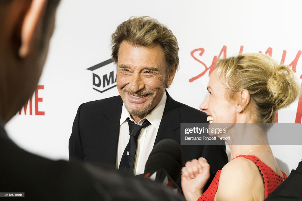 Actor/singer Johnny Hallyday and actress Sandrine Bonnaire take part to a television interview during the premiere of 'Salaud, on t'aime' (Bastard, we love you) directed by French director Claude Lelouch at Cinema UGC Normandie on March 31, 2014 in Paris, France.