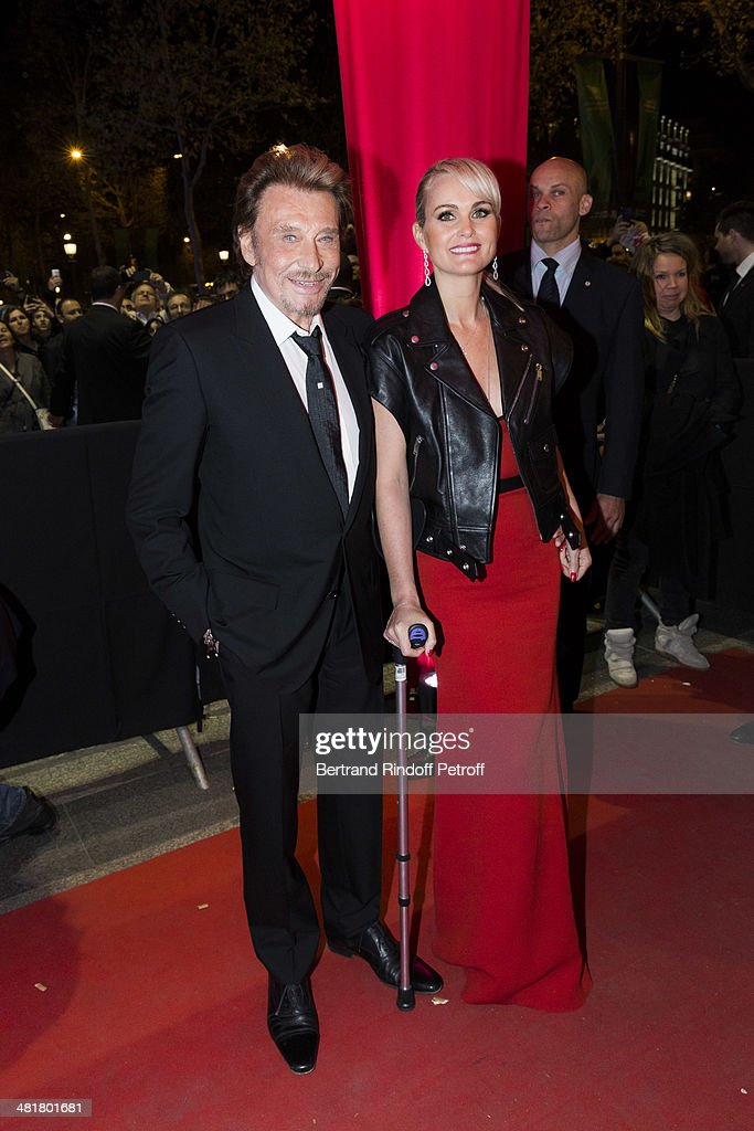 Actor/singer Johnny Hallyday (L) arrives with his wife Laeticia to the premiere of 'Salaud, on t'aime' (Bastard, we love you) directed by French director Claude Lelouch at Cinema UGC Normandie on March 31, 2014 in Paris, France.