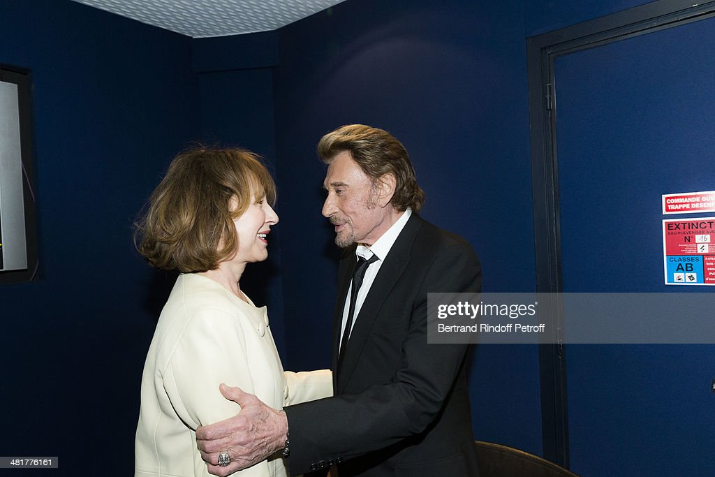 Actor/singer Johnny Hallyday (R) hugs his former partner, actress Nathalie Baye during the premiere of French director Claude Lelouch's film 'Salaud, on t'aime' (Bastard, we love you) at Cinema UGC Normandie on March 31, 2014 in Paris, France.
