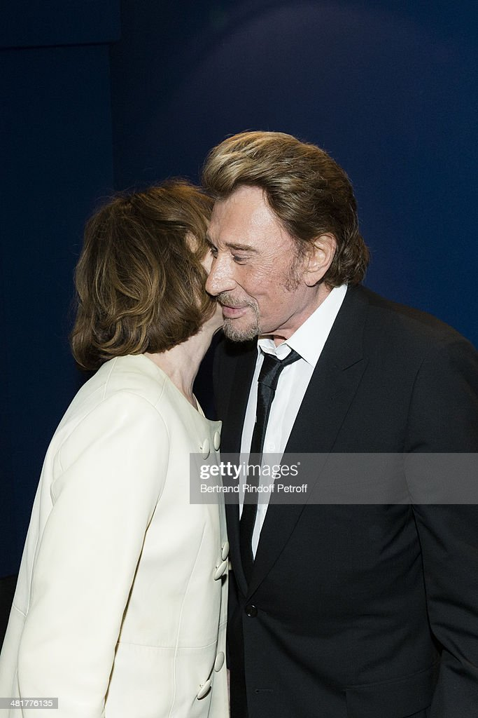 Actor/singer Johnny Hallyday (R) kisses his former partner, actress Nathalie Baye during the premiere of French director Claude Lelouch's film 'Salaud, on t'aime' (Bastard, we love you) at Cinema UGC Normandie on March 31, 2014 in Paris, France.