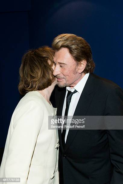 Actor/singer Johnny Hallyday kisses his former partner actress Nathalie Baye during the premiere of French director Claude Lelouch's film 'Salaud on...
