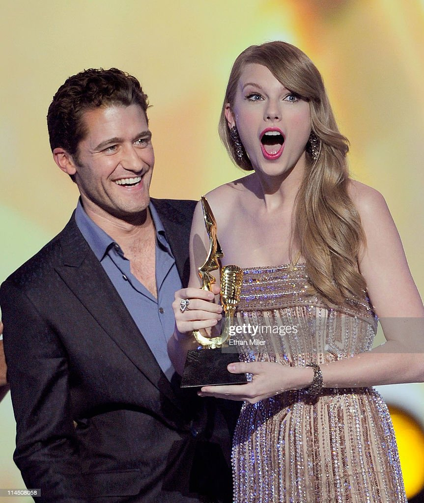 Actor/singer Matthew Morrison (L) presents the Billboard 200 Album Artist of the Year award to singer Taylor Swift onstage during the 2011 Billboard Music Awards at the MGM Grand Garden Arena May 22, 2011 in Las Vegas, Nevada.