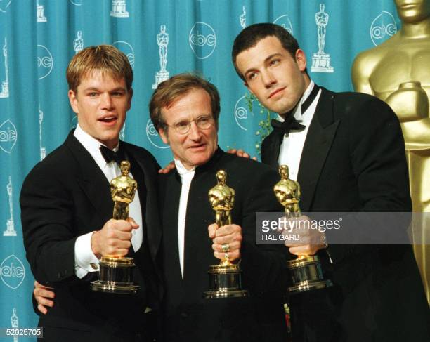 """Actors-writers Matt Damon and Ben Affleck pose with actor Robin Williams with their Oscars they won for """"Good Will Hunting"""" at the 70th Annual..."""