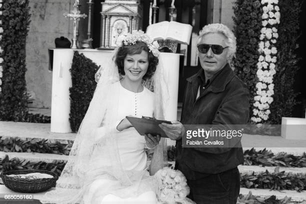 Actress Agostina Belli stands with director Dino Risi during the filming of 1976 Italian film Telefoni Bianchi The movie written and directed Risi...