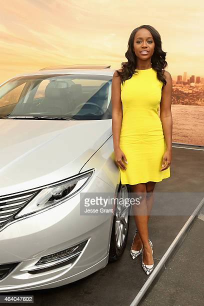 Actress Aja Naomi King poses with the Lincoln MKZ Hybrid at the Lincoln Motor Company tent during the 30th Annual Film Independent Spirit Awards at...