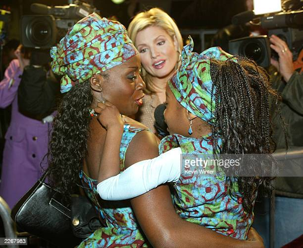 Actress Akosua Busia tends to her daughter Hadar Singleton while being interviewed at the premiere of Tears of the Sun at the Village Theater on...