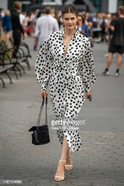 Actress Alexandra Daddario is seen wearing a black and white polka dot dress, white strappy sandals, and a black shoulder bag at the Garden of the...