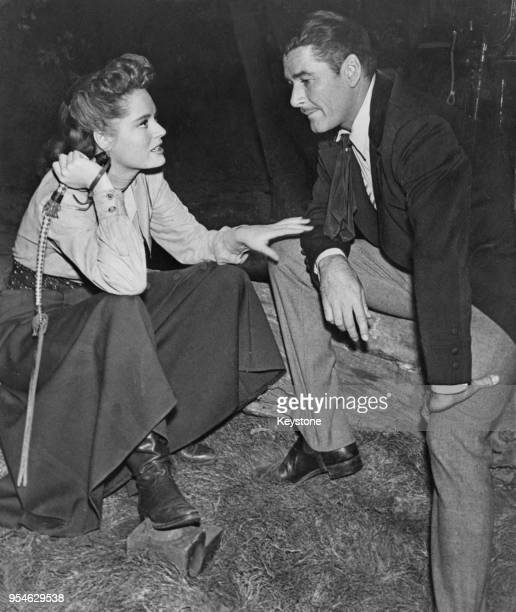 Actress Alexis Smith chats with her costar Errol Flynn on the set of the western film 'Montana' circa 1949 Flynn was at the time engaged to Romanian...