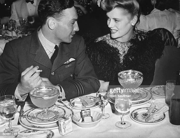 Actress Alexis Smith dining with Squadron Leader John Daring Nettleton at a party for war heroes hosted by movie actresses