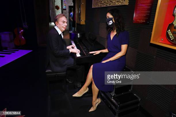 Actress Ali Ewoldt poses for a photo with a figure of Andrew Lloyd Webber in 'Madame Tussauds New York Presents Broadway' experience as Madame...