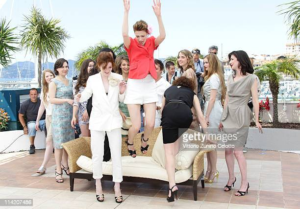 Actress Alice Barnole watches as actress Celine Sallette jumps during the L'Apollonide photocall during the 64th Annual Cannes Film Festival at...