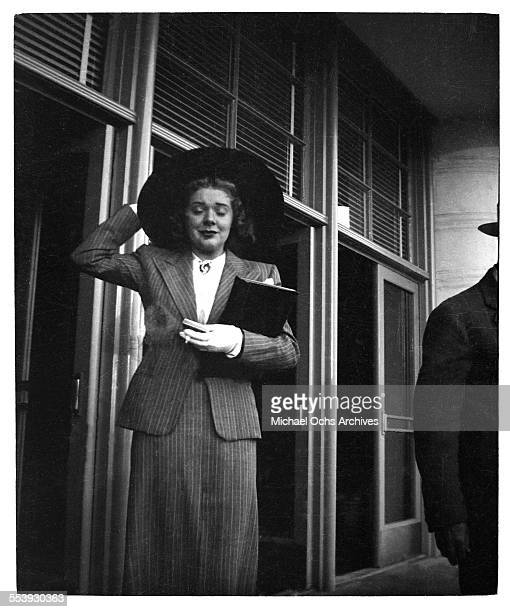 Actress Alice Faye grabs her hat as she leaves work in Los Angeles California