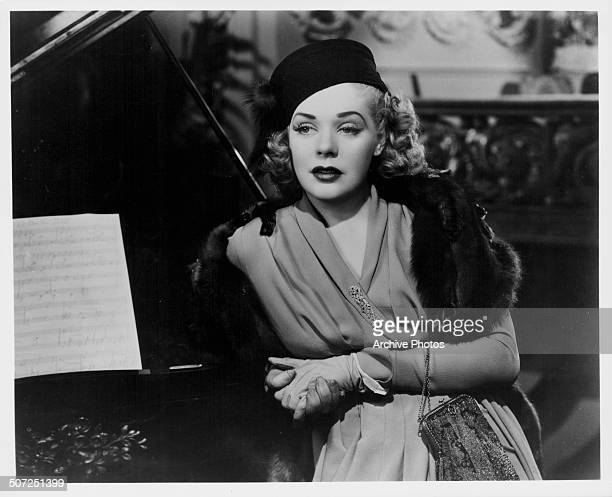 Actress Alice Faye leaning against a piano wearing a mink stole in a scene from the movie 'Alexander's Ragtime Band' 1938