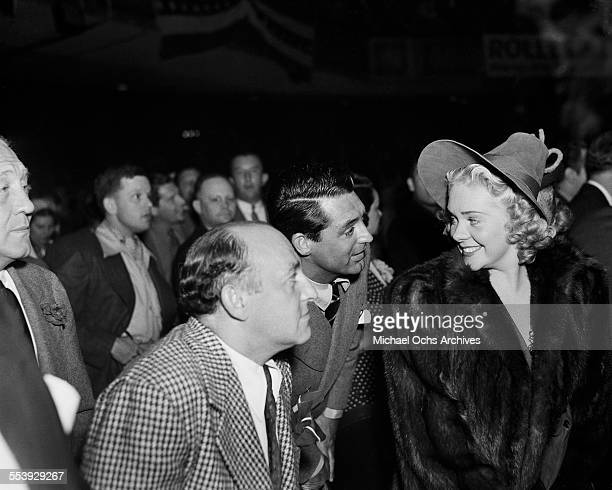 Actress Alice Faye listens director Harry Cohn and actor Cary Grant during an event in Los Angeles California
