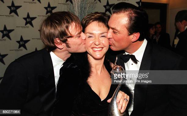Actress Amanda Burton receives a kiss from Eastenders actors Joe Absolom and Martin Kemp at The Royal Albert Hall in London during the National...