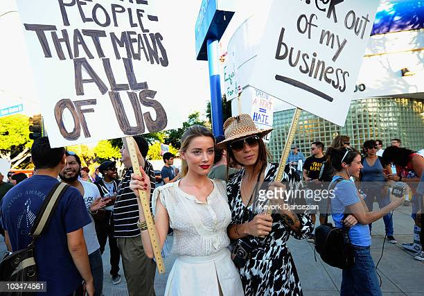 Actress Amber Heard holds a protest sign with her girlfriend Tasya Van Ree during a same-sex marriage advocates demonstration against the stay...