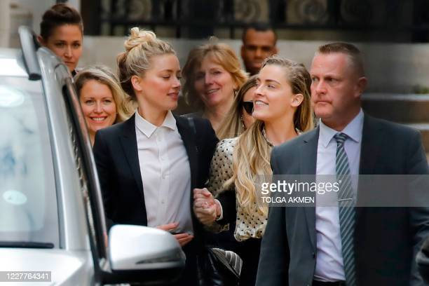 US actress Amber Heard leaves handinhand with her sister Whitney Heard from the High Court after a hearing in the libel trial by her former husband...