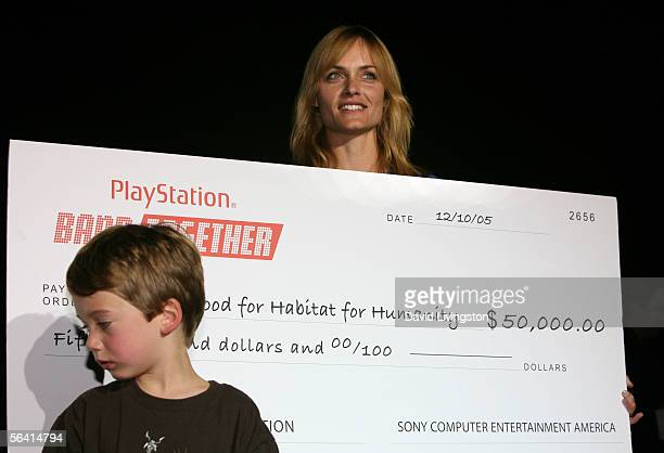Actress Amber Valletta and son Auden McCaw present a check during Playstation BANDtogether a benefit presented by Sony Computer Enterainment America...