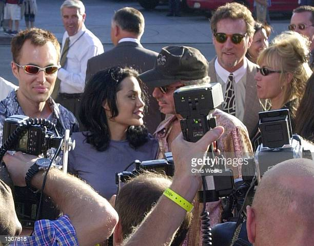 Actress and cast member Angelina Jolie and her husband actor Billy Bob Thornton center are surrounded by paparazzi June 5 2000 at the world premiere...