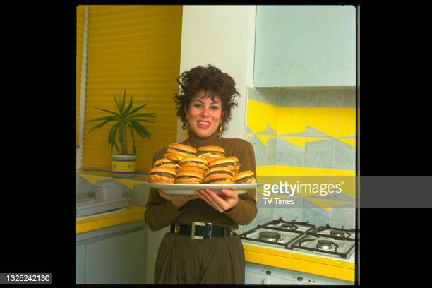 Actress and comedian Ruby Wax holding a plate of hamburgers, circa 1987.