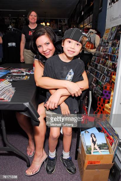 Actress and current Playboy model Christa Campbell poses with a young fan at an autograph party for the new graphic novel '2001 Maniacs' held at the...