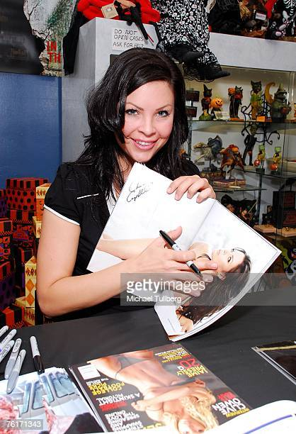 Actress and current Playboy model Christa Campbell tries to cover up her new Playboy magazine photo spread at an autograph party for the new graphic...