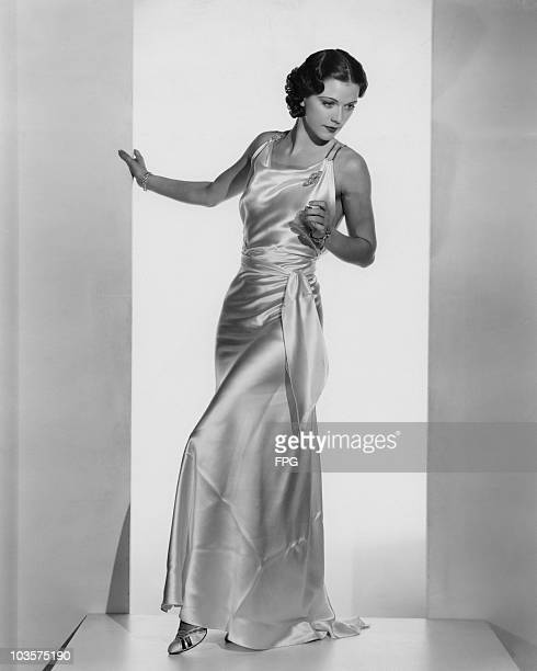 Actress and dancer Eleanor Powell pictured wearing a white satin formal gown USA circa 1935 The gown features a double rhinestone band with the split...