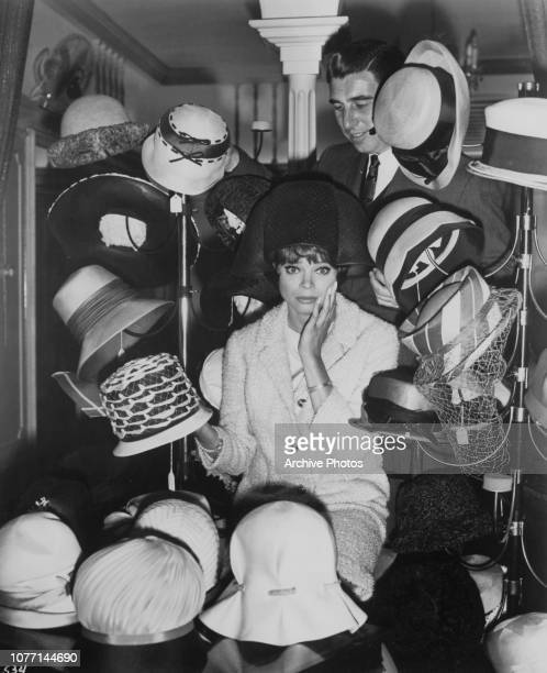 Actress and dancer Juliet Prowse is overwhelmed by a choice of hats circa 1960