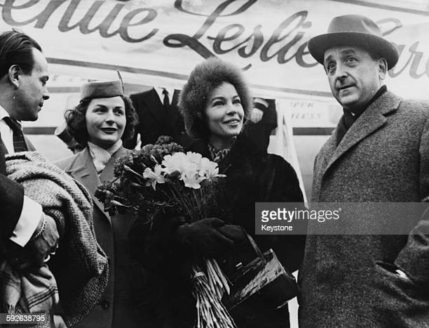 Actress and dancer Leslie Caron is greeted by a bouquet of flowers and MGM Chief Beerman as she arrives for the premiere of the film 'Gigi' Frankfurt...
