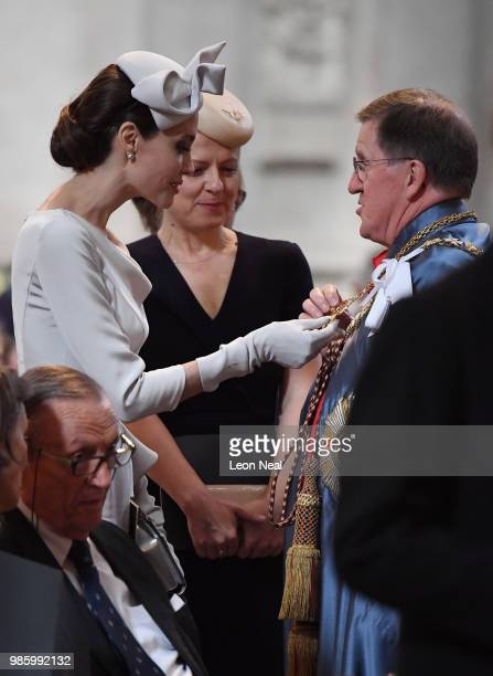 Actress and director Angelina Jolie looks at a part of the formal robes of George Robertson after arriving ahead of the Order Of St George 200th...