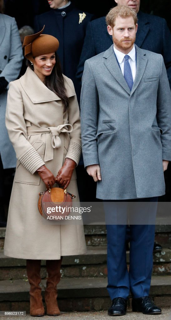 US actress and fiancee of Britain's Prince Harry Meghan Markle (L) and Britain's Prince Harry (R) stand together as they wait to see off Britain's Queen Elizabeth II after attending the Royal Family's traditional Christmas Day church service at St Mary Magdalene Church in Sandringham, Norfolk, eastern England, on December 25, 2017. / AFP PHOTO / Adrian DENNIS