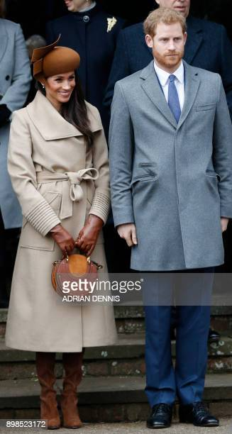 US actress and fiancee of Britain's Prince Harry Meghan Markle and Britain's Prince Harry stand together as they wait to see off Britain's Queen...