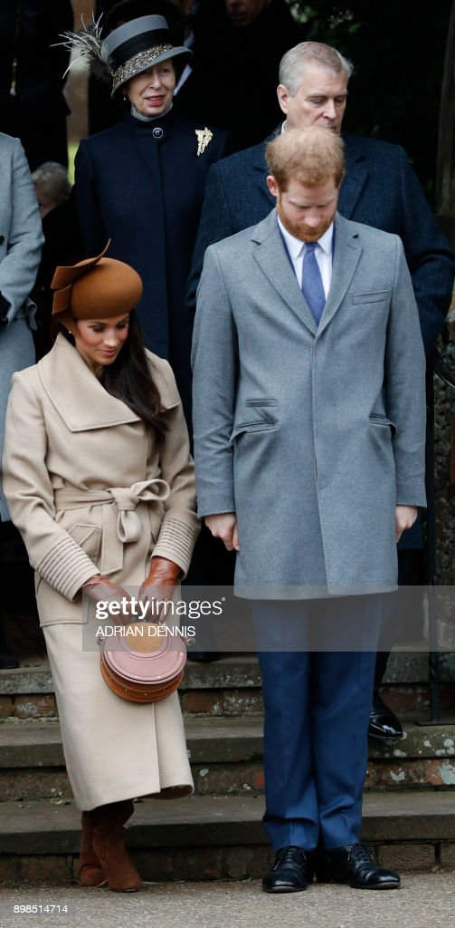 US actress and fiancee of Britain's Prince Harry Meghan Markle (L) curtseys as Britain's Prince Harry (R) bows as they see off Britain's Queen Elizabeth II leaving after the Royal Family's traditional Christmas Day church service at St Mary Magdalene Church in Sandringham, Norfolk, eastern England, on December 25, 2017. / AFP PHOTO / Adrian DENNIS