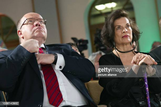 Actress and human rights activist Bianca Jagger sits next to German Environment Minister Peter Altmaier during the opening of the exhibition 'Ihrer...