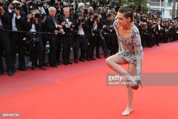 Actress and member of the Feature Film Jury Kristen Stewart removes her shoes on the red carpet as she arrives on May 14, 2018 for the screening of...
