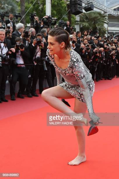 US actress and member of the Feature Film Jury Kristen Stewart removes her shoes on the red carpet as she arrives on May 14 2018 for the screening of...