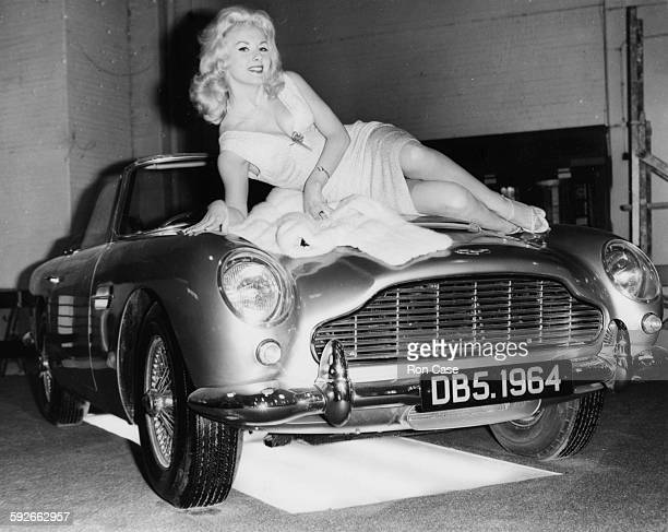 Actress and model Barbara Roscoe lying across the bonnet of the new Aston Martin DB5 car at the Motor Show in Earls Court London October 15th 1963