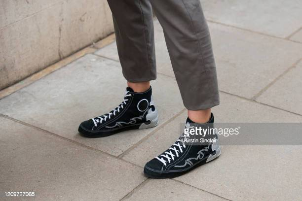Actress and Model Ella Rae Smith wears a Dak's suit and Converse trainers during London Fashion Week February 2020 on February 18 2020 in London...