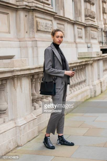 Actress and model Ella Rae Smith wears a Dak's suit Converse shoes Jill Sander bag Vintage necklace and Anthropologie earrings during London Fashion...