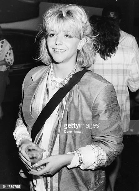 Actress and model Leslie Ash holding a drink at a party circa 1988
