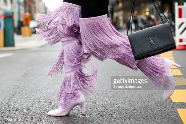 Actress and model Rebecca Kunikowski wearing a black bag by Saint Laurent black pants with layered light purple fringe by Bcbgmaxazria and light...